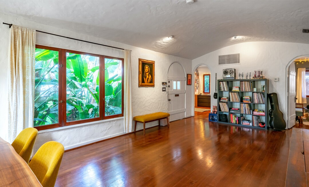The cozy Spanish-style home expands to a grassy yard and remodeled studio used as a music room.