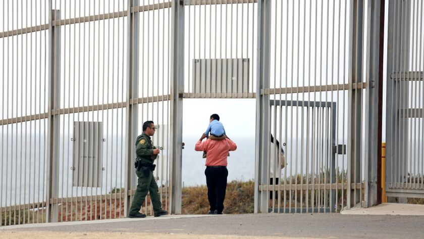 A U.S. Border Patrol agent escorts a family through the secondary fence back to Border Field State P
