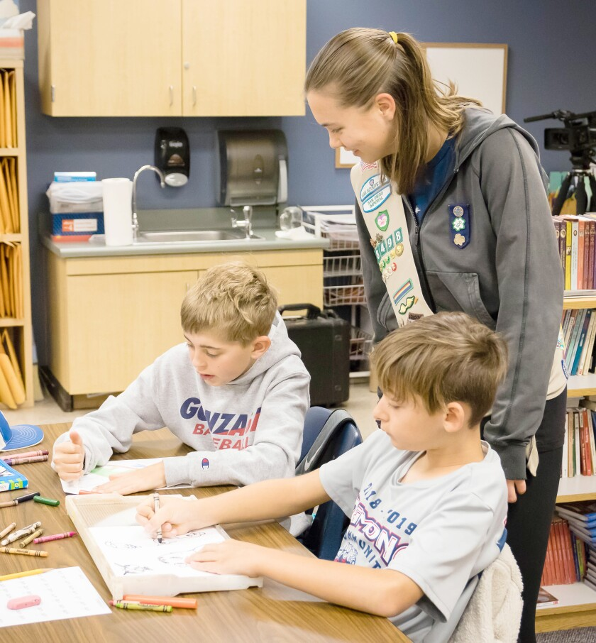 Girl Scout Helen Buchanan teaches Mountain Valley Academy students Brett Sturgeon, left, and Korban Steinberg about the importance of protecting bees.