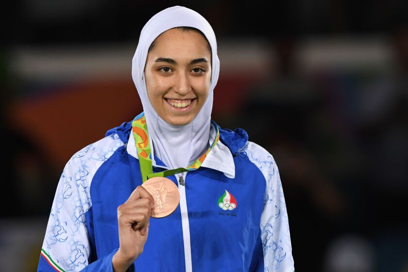 Iran's Kimia Alizadeh poses on the podium after winning a bronze medal in taekwondo at the Rio de Janeiro 2016 Olympic Games.