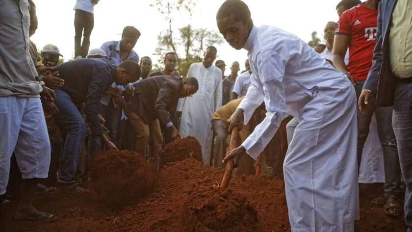 Mourners bury the body of Feisal Ahmed near to the grave of his colleague Abdalla Dahir, who were bo
