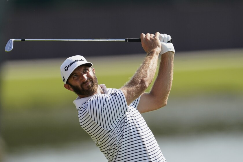 Dustin Johnson hits from the fairway on the 8th hole during the third round of the Tour Championship golf tournament at East Lake Golf Club in Atlanta, Sunday, Sept. 6, 2020. (AP Photo/John Bazemore)