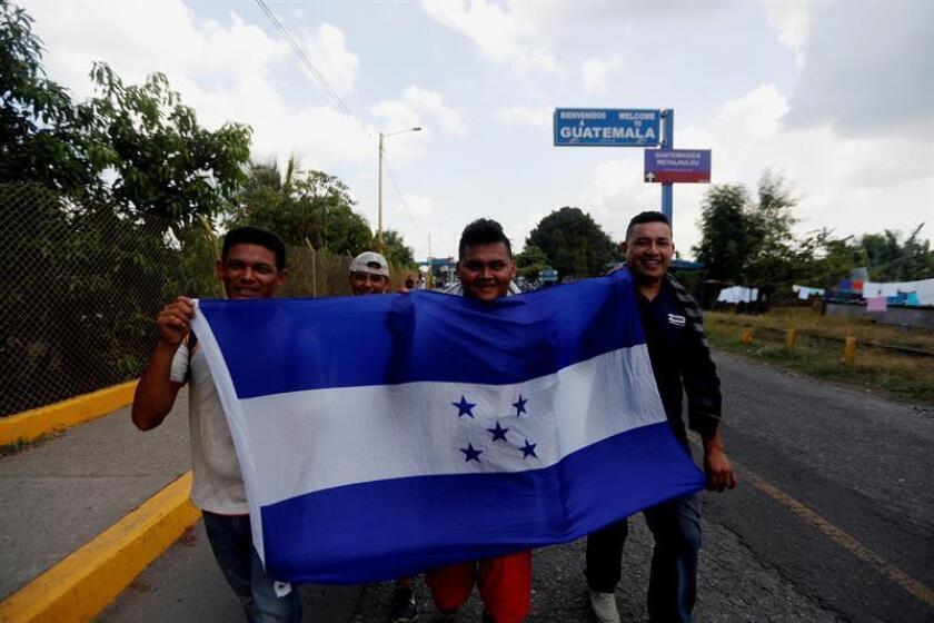 Cuatro jóvenes hondureños caminan este jueves hacia territorio mexicano con la bandera de Honduras después de pasar la frontera de Guatemala. EFE