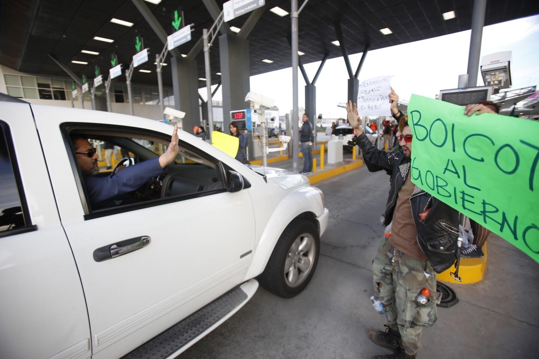 Tijuana Baja California, Mexico, January 8th, 2017: | Jesus Navaro waving at car passing through. | (Alejandro Tamayo, The San Diego Union-Tribune)