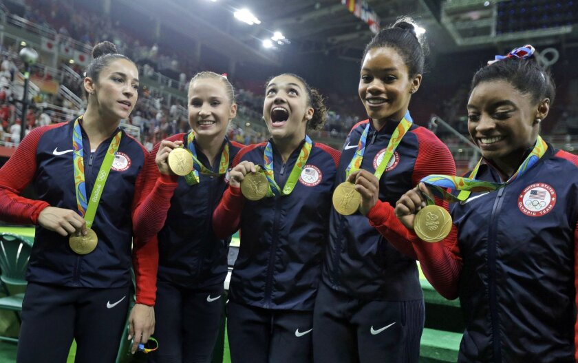U.S. gymnasts and gold medallists, right to left, Simone Biles, Gabrielle Douglas, Lauren Hernandez, Madison Kocian and Aly Raisman pose for photographs during the medal ceremony for the artistic gymnastics women's team at the 2016 Summer Olympics in Rio de Janeiro, Brazil, Tuesday, Aug. 9, 2016. (