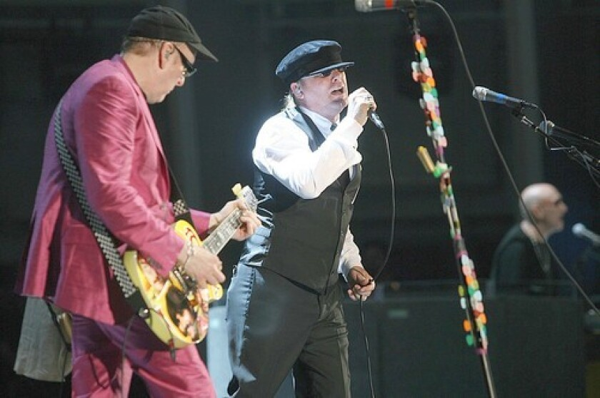 Cheap Trick guitarist Rick Nielsen (left) and lead singer Robin Zander (center) are shown in concert at the Hollywood Bowl.