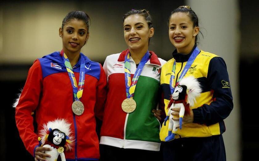 La mexicana Ahtziri Viridia Sandoval (c), medalla de oro, la cubana Marcia Tereza Vidiaux (i), medalla de plata, y la colombiana Valentina Pardo, bronce, posan en la premiación de barras asimétricas hoy, lunes 23 de julio de 2018, en los XXIII Juegos Centroamericanos y del Caribe Barranquilla 2018 en Barranquilla (Colombia). EFE