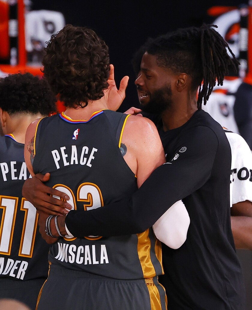 Nerlens Noel hugs Mike Muscala, left, of the Oklahoma City Thunder after Muscala hit the game-winning three-point basket against the Miami Heat during the second half of an NBA basketball game Wednesday, Aug. 12, 2020, in Lake Buena Vista, Fla. (Kevin C. Cox/Pool Photo via AP)