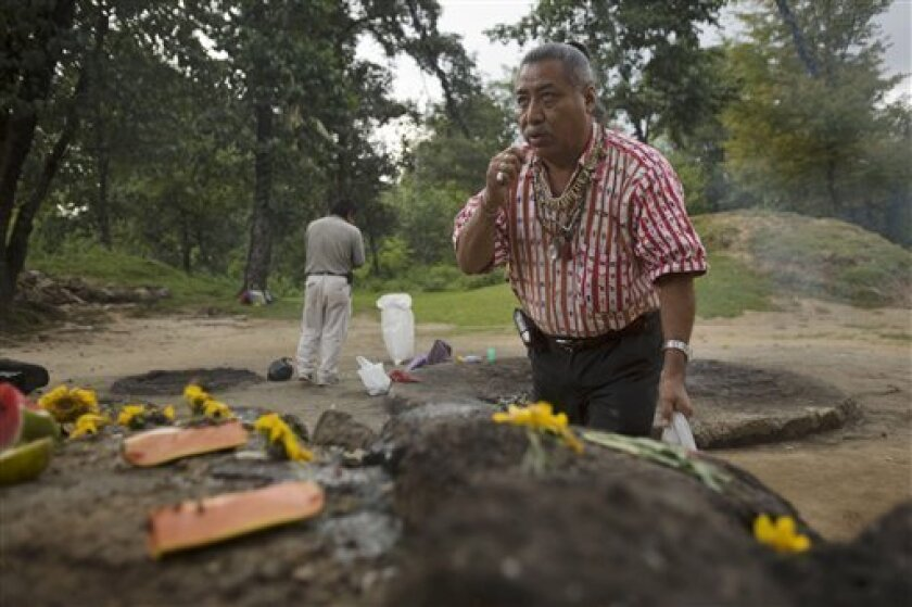"""In this photo taken Oct. 3, 2009, Guatemalan Mayan Indian elder Apolinario Chile Pixtun gestures as he pays his respects at an altar within the Iximche ceremonial site in Tecpan, Guatemala. Archaeologists, astronomers and modern-day Mayas shrug off the popular frenzy over the date of 2012, predicting it will bring nothing more than a meteor shower of new-age """"consciousness,"""" pseudo-science and alarmist television specials. (AP Photo/Moises Castillo)"""