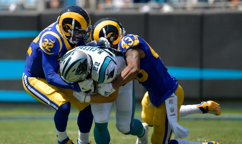 Rams safeties Eric Weddle, left, and John Johnson tackle Carolina Panthers running back Christian McCaffrey during the Rams' season opener.