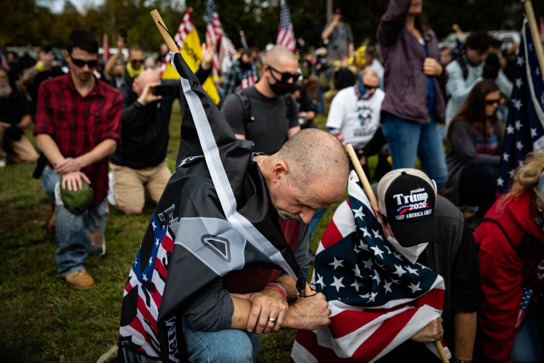 People with U.S. flags and Trump 2020 hats kneel in a park