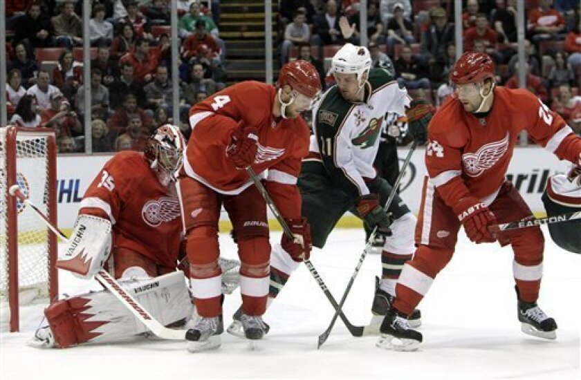 Detroit Red Wings goalie Jimmy Howard (35) stops a Minnesota Wild center Kyle Brodziak (21) shot as Red Wings defensemen Jakub Kindl (4), of the Czech Republic, and Ruslan Salei (24), of Belarus, defend in the first period of an NHL hockey game in Detroit, Sunday, April 3, 2011. (AP Photo/Paul Sancya)