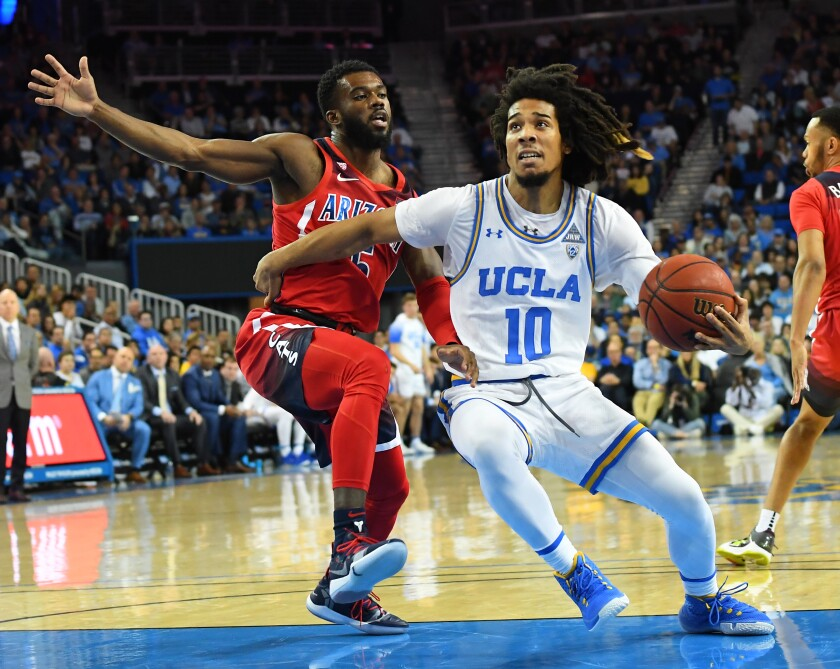 Arizona's Max Hazzard (5) guards UCLA's Tyger Campbell (10) as he drives to the basket in the first half at Pauley Pavilion on Saturday.