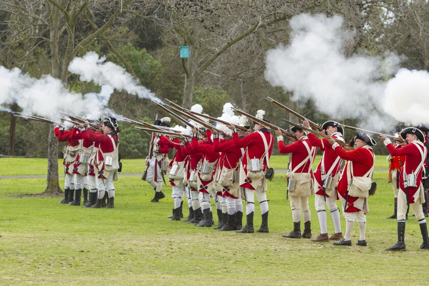 Members of the British army fire during an American Revolutionary War reenactment in Huntington Beach in 2018. Another will be held Saturday and Sunday at Huntington Beach's Central Park.