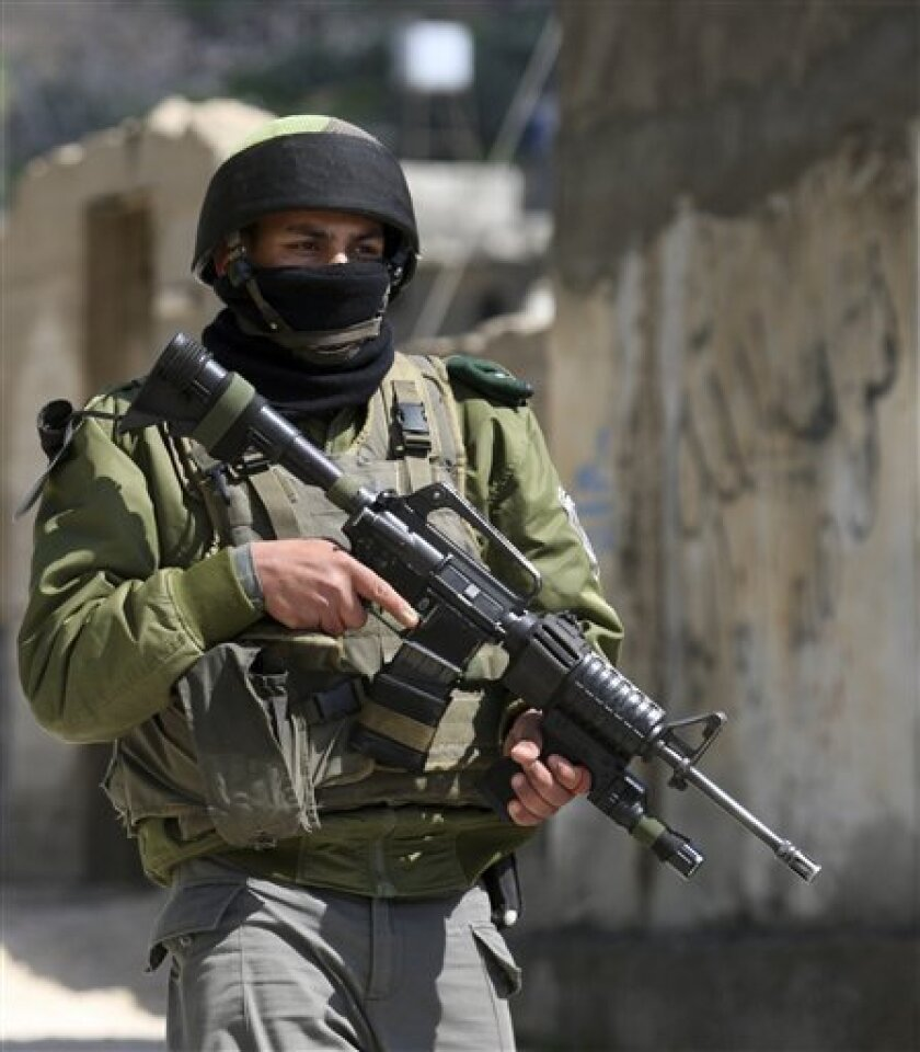 An Israeli border police officer patrols the West Bank village of Awarta, after five people were killed in the nearby Jewish settlement of Itamar Saturday, March 12, 2011. A Palestinian infiltrated Itamar early Saturday and killed five people, the Israeli military said. Israeli media is reporting that the dead are all members of the same family with parents and three children aged 11, 3 and an infant, all reported to have been stabbed while they slept. (AP Photo/Nasser Ishtayeh)