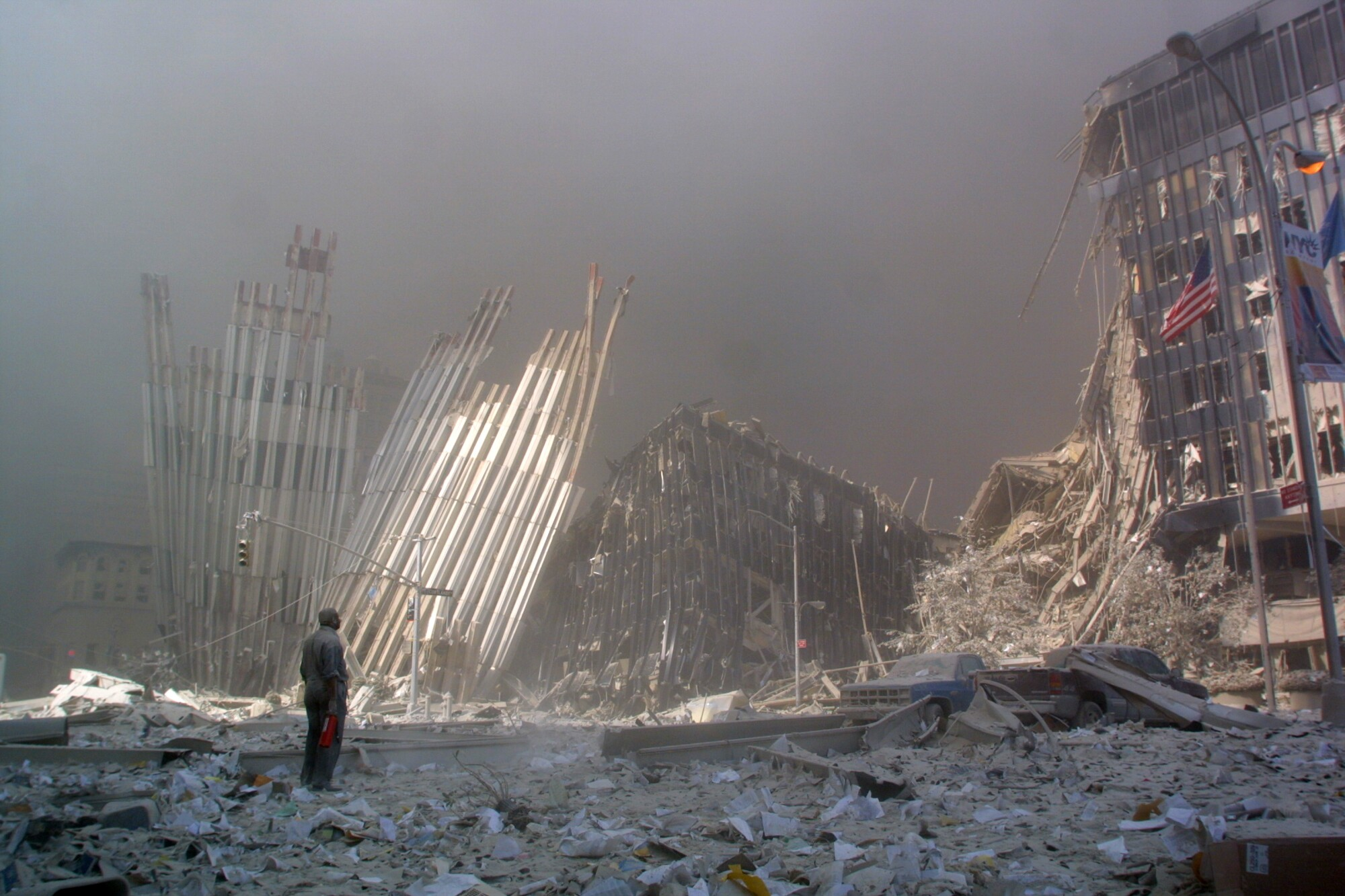A man stands surrounded by debris, with an American flag on a pole nearby