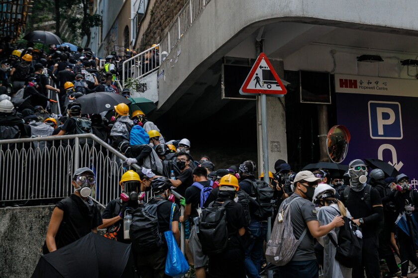 Pro-democracy demonstrators in Hong Kong retreat from police.