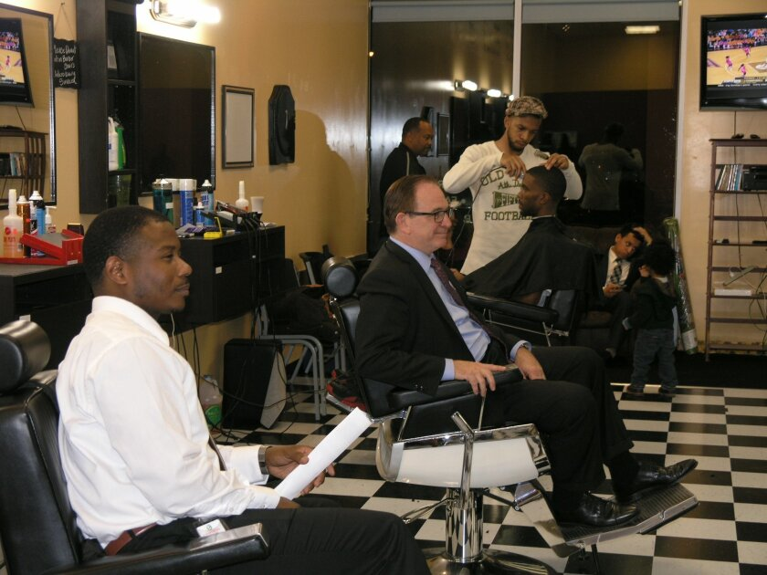 Senate Republican Leader Bob Huff of Diamond Bar (center) sits in a barber chair at CeCe's Cutz in Sacramento during a Feb. 23 Barbershop Town Hall to discuss policing and other issues. Huff has proposed a bill requiring police agencies that adopt body camera requirements to establish public policies for using them.