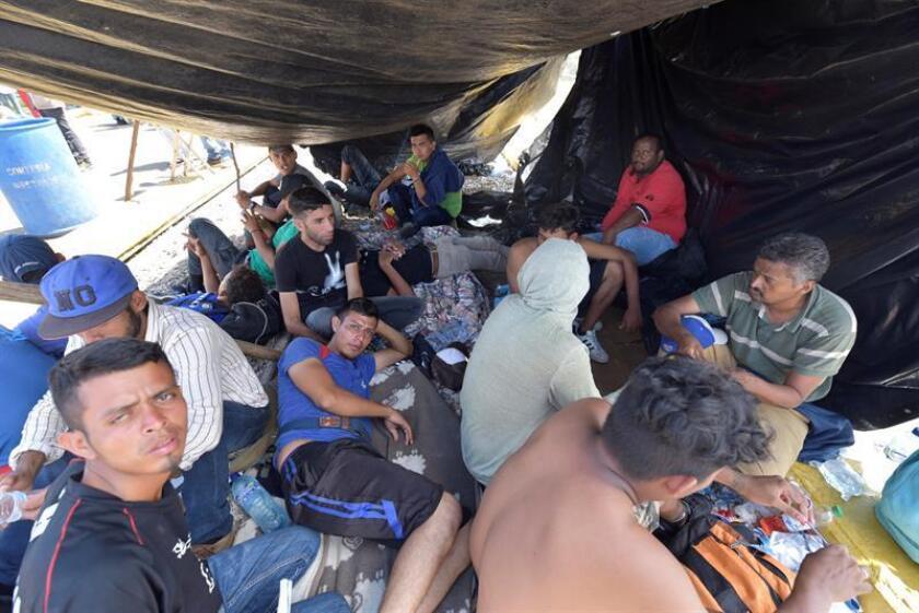 Migrantes hondureños permanecen en el puente internacional Rodolfo Robles, que cruza el Río Suchiate, que une a México con Guatemala, en el estado de Chiapas (México) hoy, lunes 22 de octubre de 2018. EFE