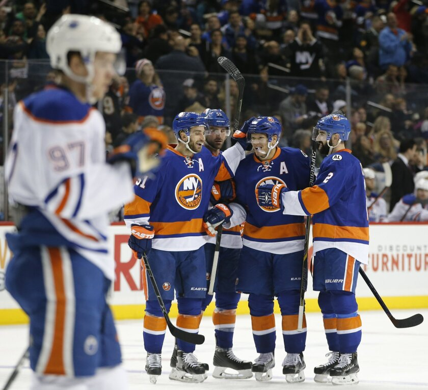 Edmonton Oilers center Connor McDavid (97) skates away as New York Islanders teammates celebrate with right wing Kyle Okposo (21) after Okposo scored a goal in the second period of an NHL hockey game in New York, Sunday, Feb. 7, 2016. (AP Photo/Kathy Willens)