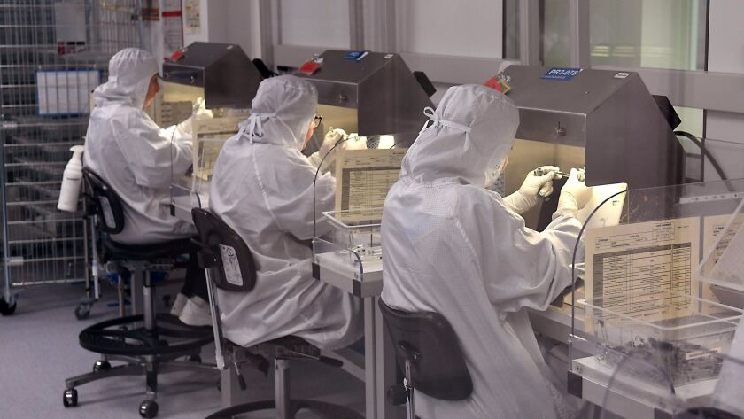 Lab workers examine samples at an Allergan research site in France. A U.S. judge has cast doubt on the company's scheme to protect its drug patents by trading them to a New York Indian tribe.