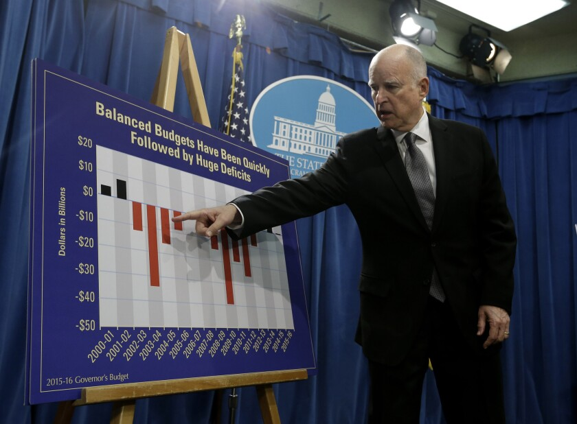 During a Jan. 9 briefing in Sacramento, Gov. Jerry Brown points to a chart showing the ups and downs in California's finances in the last 15 years.