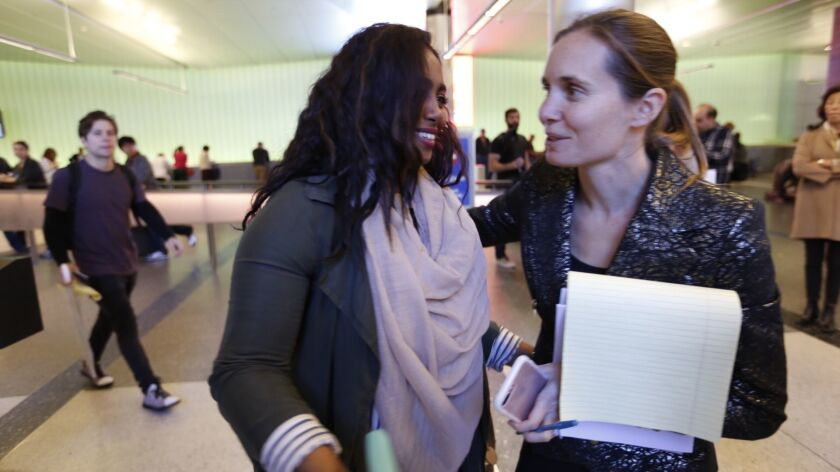 Areej Ali, left, thanks attorney Courtney Black after she was detained upon her arrival from Sudan.