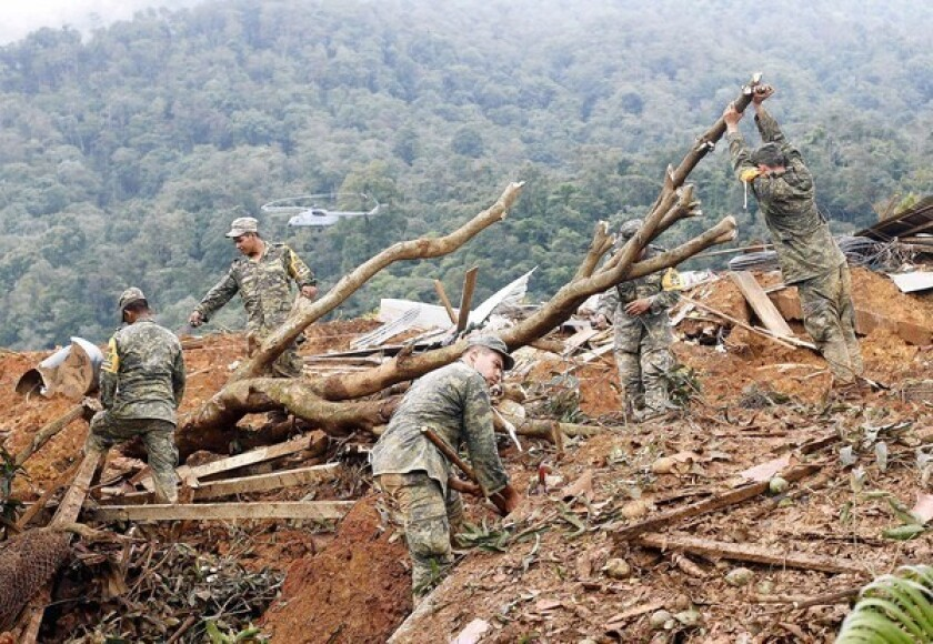 Mexican soldiers work in La Pintada after a rain-driven mudslide swept away residents and homes.