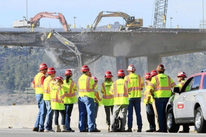 A crew watches as part of the Mullholland Drive bridge over the 405 Freeway is demolished.