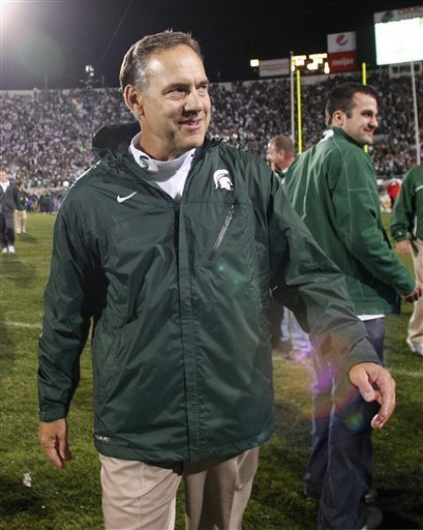 FILE - This Sept. 18, 2010, file photo shows Michigan State coach Mark Dantonio smiling as he leaves the field following a 34-31 overtime win over Notre Dame in an NCAA college football game, in East Lansing, Mich. Dantonio plans to be in a coaching box above the field Saturday when the No. 24 Spartans face No. 11 Wisconsin, just two weeks after he was hospitalized following a mild heart attack. (AP Photo/Al Goldis, File)