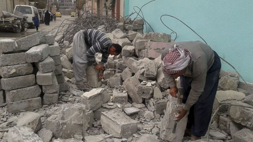 Fouad Salim, left, and Khalef Attiyeh, chip at chunks of concrete recovered from a destroyed home to