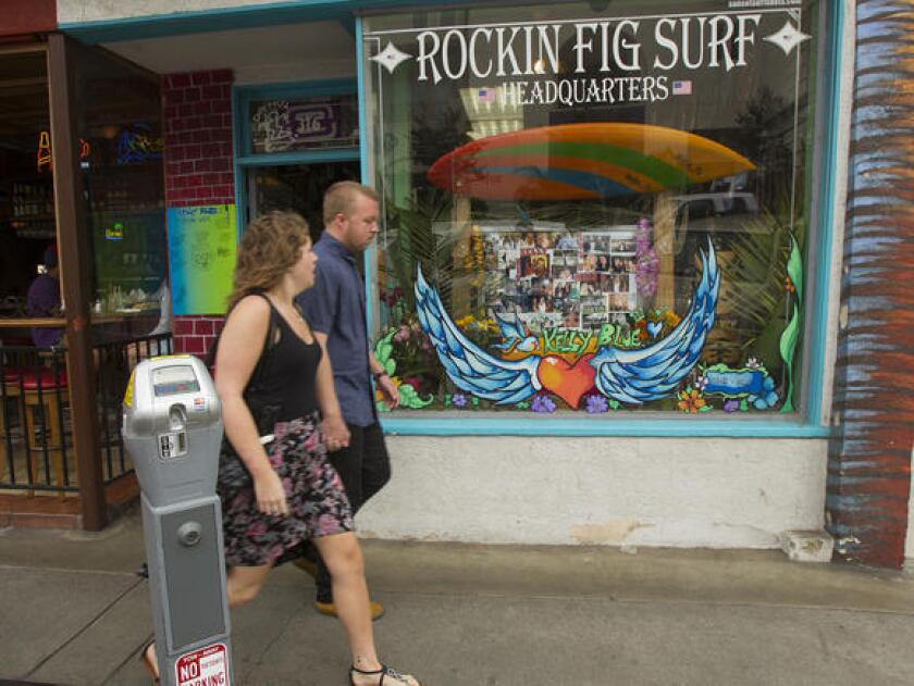 Pedestrians pass a store window memorial for Kelly Morehouse at Rockin Fig Surf Headquarters in Huntington Beach on Monday.