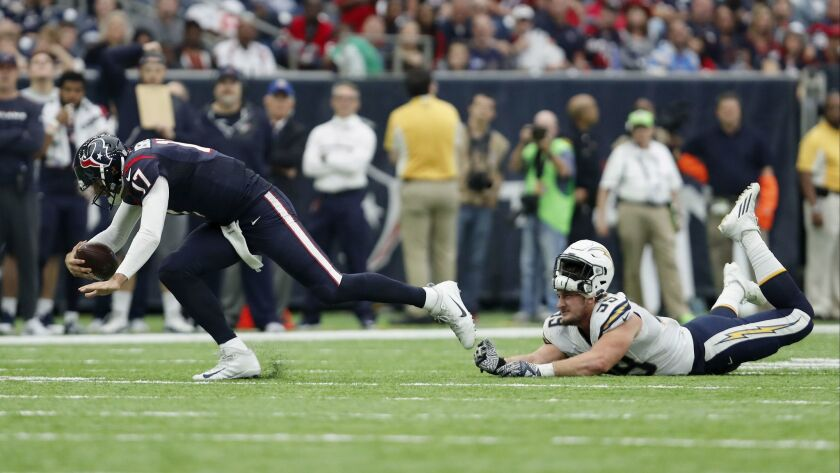 Chargers DE Joey Bosa loses his helmet as he trips up Texans QB Brock Osweiler in the fourth quarter at NRG Stadium on Nov. 27, 2016 in Houston, Texas. (Photo by Tim Warner/Getty Images) ** OUTS - ELSENT, FPG, CM - OUTS * NM, PH, VA if sourced by CT, LA or MoD **