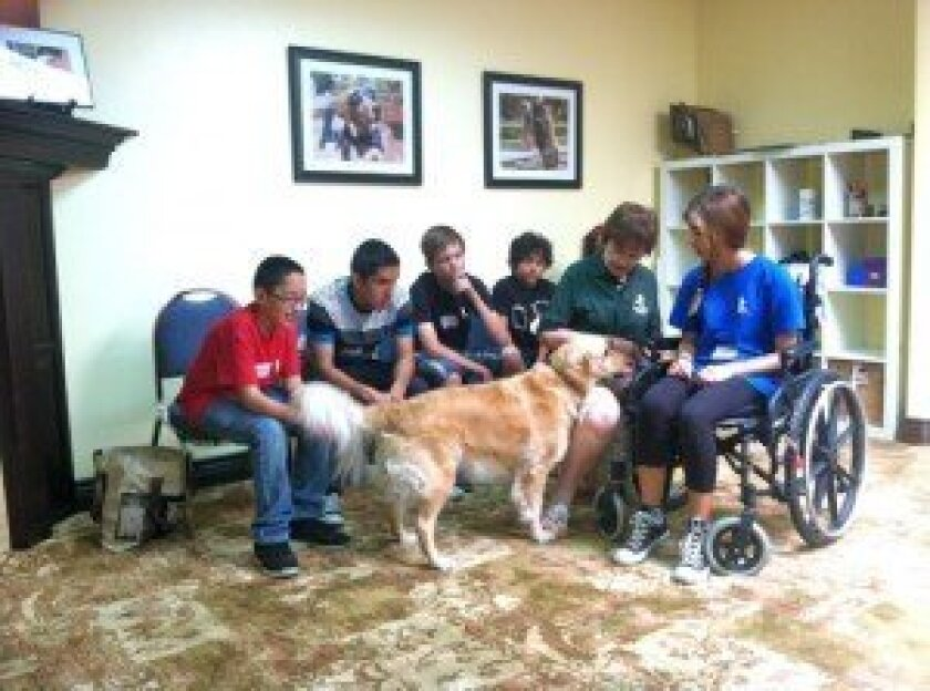 Kids Korps volunteers learning how to train therapy dogs from Paws'itive Teams handler.