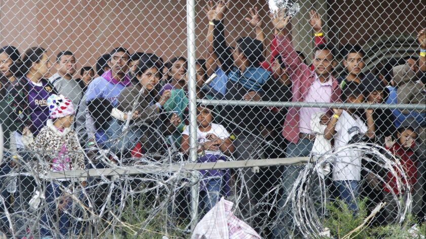 FILE - In this March 27, 2019, file photo, Central American migrants wait for food in a pen erected