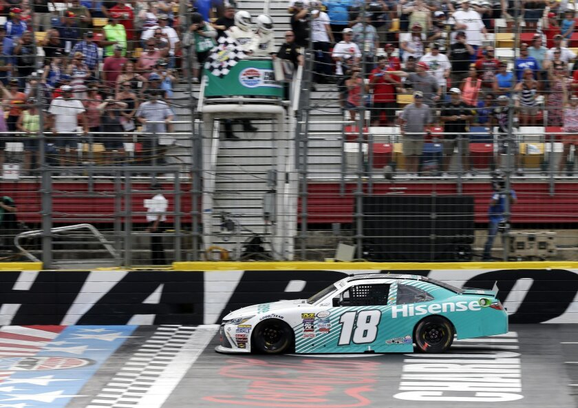 Denny Hamlin takes the checkered flag to win the NASCAR Xfinity series auto race at Charlotte Motor Speedway in Concord, N.C., Saturday, May 28, 2016. (AP Photo/Chuck Burton)