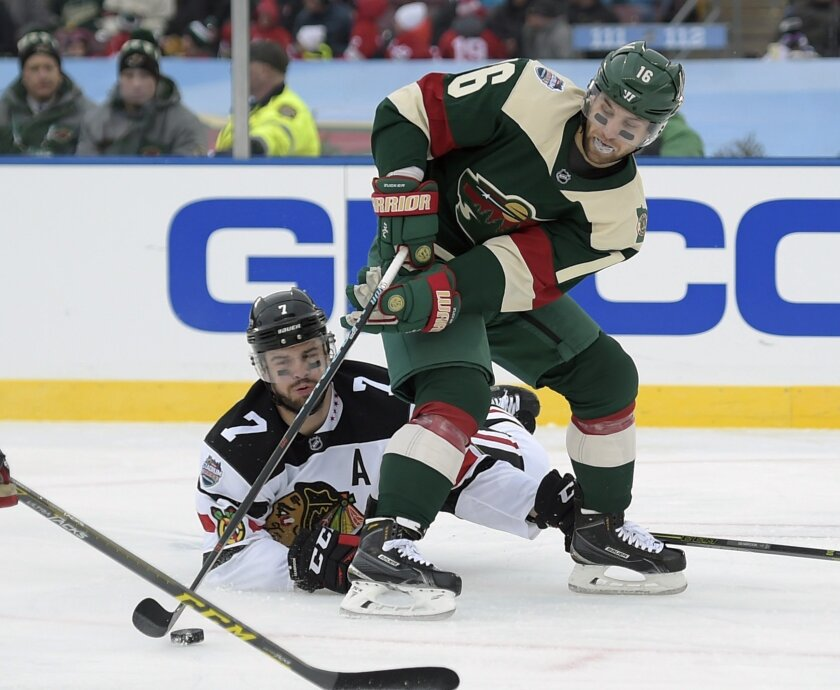 Minnesota Wild left wing Jason Zucker, right, keeps the puck away from Chicago Blackhawks defenseman Brent Seabrook during the second period of an NHL Stadium Series hockey game Sunday, Feb. 21, 2016, in Minneapolis. (AP Photo/Craig Lassig)