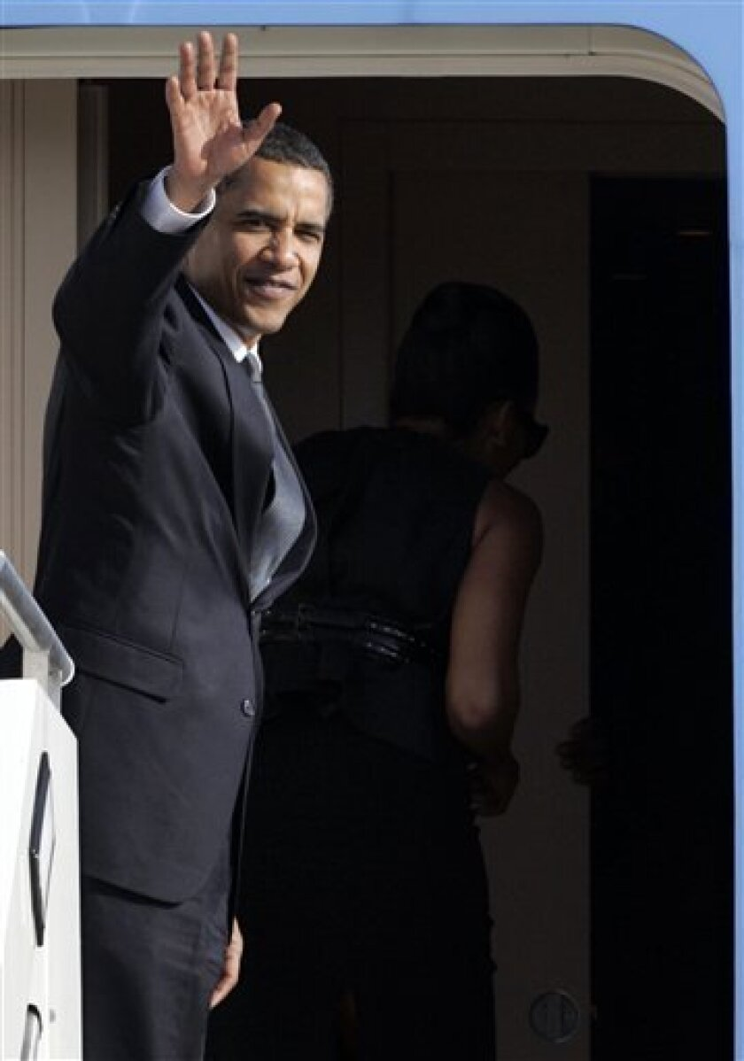President Barack Obama waves as he embarks Air Force One with first lady Michelle, in background partially visible, at Pratica di Mare's military airport, near Rome, Friday, July 10, 2009. After attending a three-day G8 (Group of Eight) Summit meeting in L'Aquila, central Italy, President Obama sat down with Pope Benedict XVI at the Vatican on Friday for a meeting in which frank but constructive talks were expected between two men who agree on helping the poor but disagree on abortion and stem cell research. (AP Photo/Riccardo De Luca)