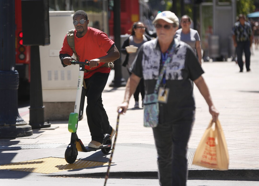 SAN DIEGO, CA 9/14/2018: An electric scooter rider gets ready to cross Broadway at the corner of Fou