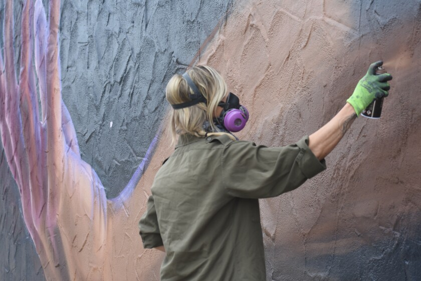 Muralist Carly Ealey finishes a mural on Palm Avenue and Florence Street in Imperial Beach on Tuesday.