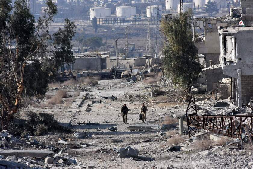Syrian pro-government forces patrol an Aleppo district Dec. 12 after troops retook the area from rebel fighters.