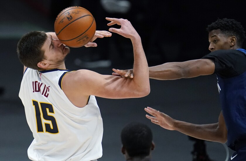 Denver Nuggets center Nikola Jokic, left, is hit by the ball after being fouled by Minnesota Timberwolves guard Jarrett Culver during the second half of an NBA basketball game Tuesday, Jan. 5, 2021, in Denver. (AP Photo/David Zalubowski)