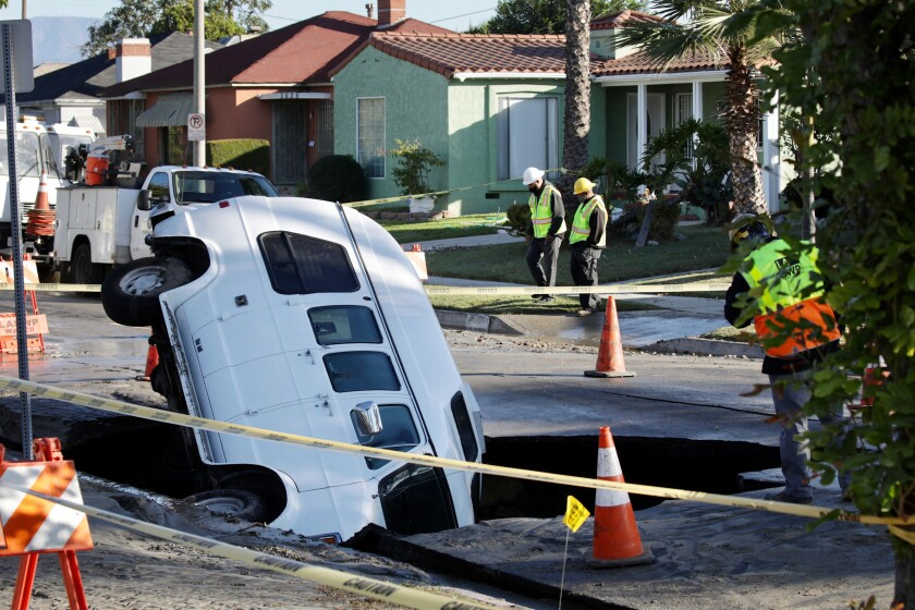 A van fell into a sinkhole in South Los Angeles early Tuesday morning created by a water main break