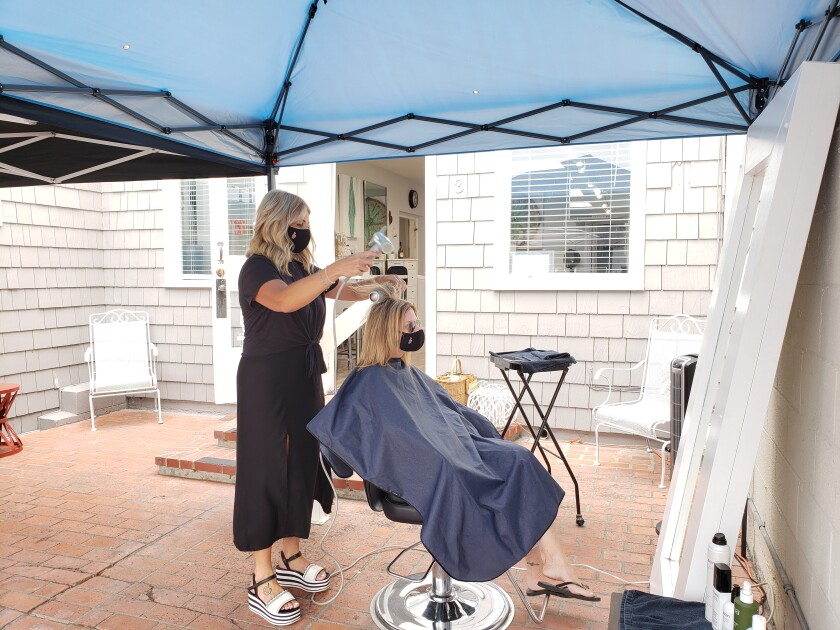 Stephanie Marquez styles a client's hair on the patio of The Boulevard salon in La Jolla.