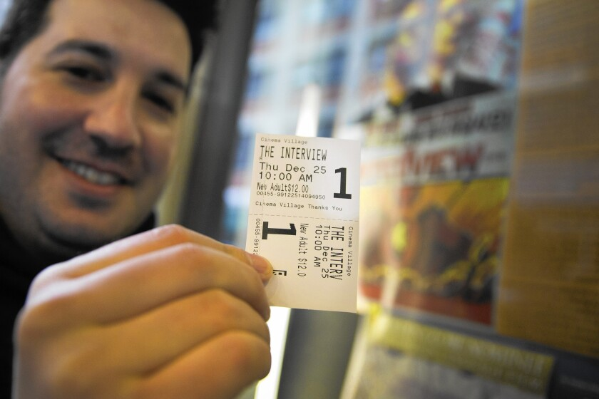"""Derek Karpel holds his ticket to a screening of """"The Interview"""" at Cinema Village movie theater in New York on Christmas Day."""