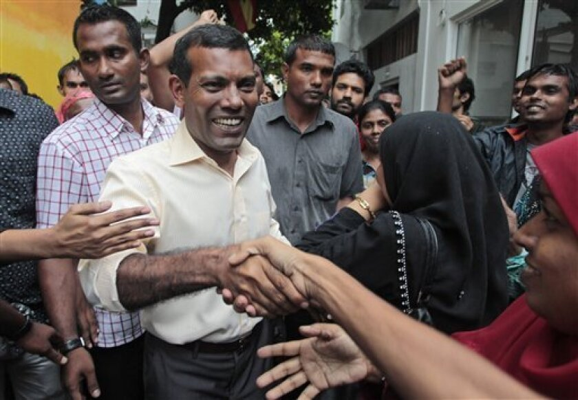 Former Maldivian president Mohamed Nasheed greets supporters outside his residence in Male, Maldives, Thursday, Feb. 9, 2012. A Maldives court issued an arrest warrant Thursday for Nasheed, one day after his supporters rampaged in the capital and his claim of being ousted by a coup left unclear the stability of the fledging Indian Ocean democracy. (AP Photo/Eranga Jayawardena)