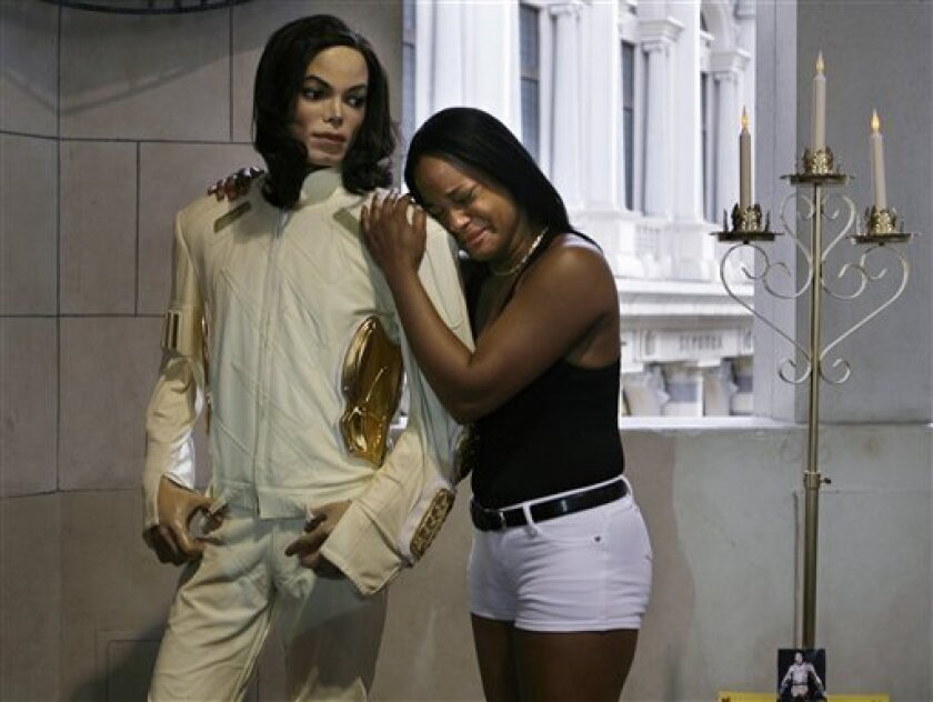 FILE - In this June 25, 2009 file photo, Shayla Ivy cries as she holds a wax replica of Michael Jackson outside of Madame Tussaud's Wax Museum at The Venetian Hotel and Casino in Las Vegas the day Jackson died. Jackson's stunning death made him Yahoo's biggest star this year, propelling him to the top of the Internet company's annual breakdown of the most frequent online search requests. The list released Tuesday Dec. 1, 2009 is meant to provide a reading on our cultural pulse. (AP Photo/Laura Rauch, File)