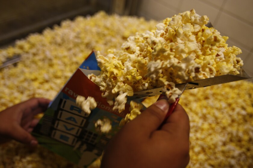 A concession worker scoops up popcorn