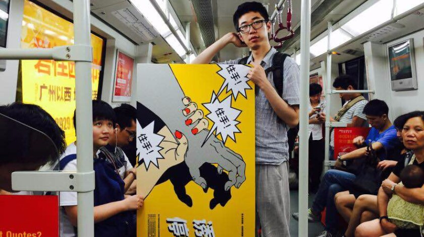 A feminist activist carries an anti-sexual harassment poster on the Guangzhou subway.