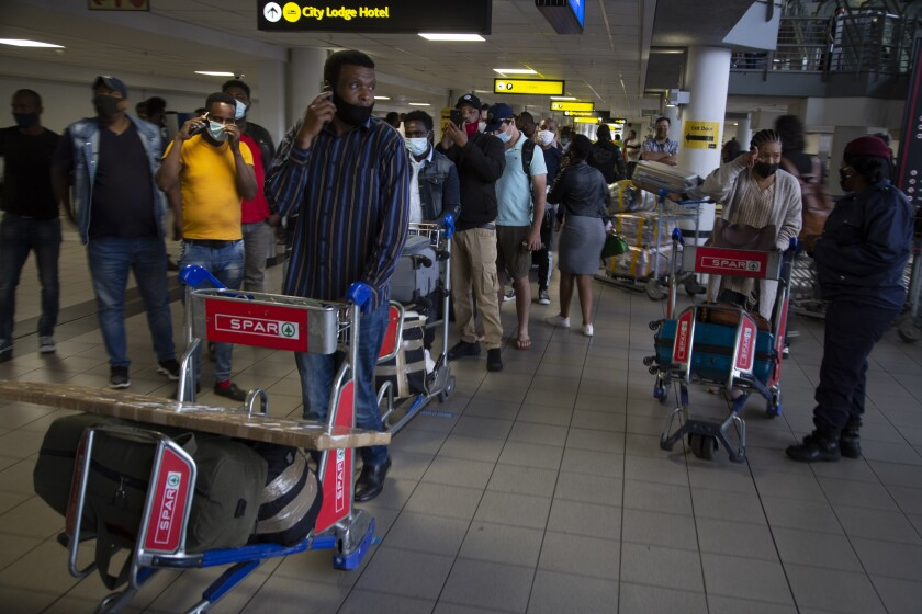 FILE — In this Oct.1, 2020 file photo passengers queue to access the O.R. Tambo Airport in Johannesburg, South African travel agencies are reporting a surge in reservations for travel to and from Britain ahead of the country being removed from the U.K.'s COVID-19 red list next week. (AP Photo/Denis Farrell/File)